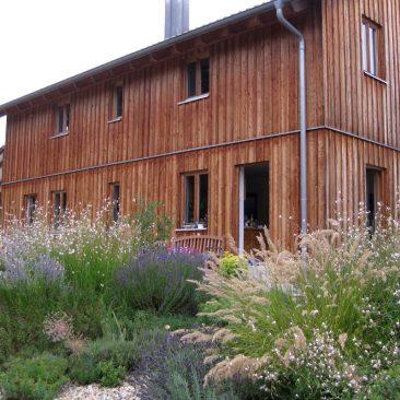 Holzhaus und seine pflanzlichen Begleiter