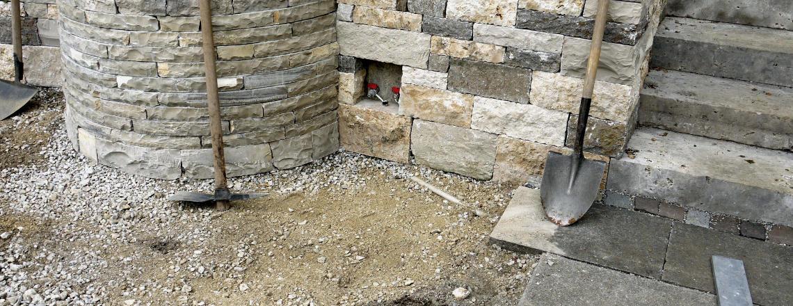 Brunnen in Natursteinmauer integriert